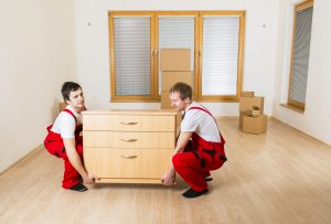 Two movers in red overalls moving furniture.